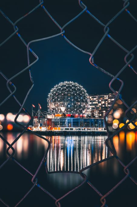 Illuminated silver dome behind a fence