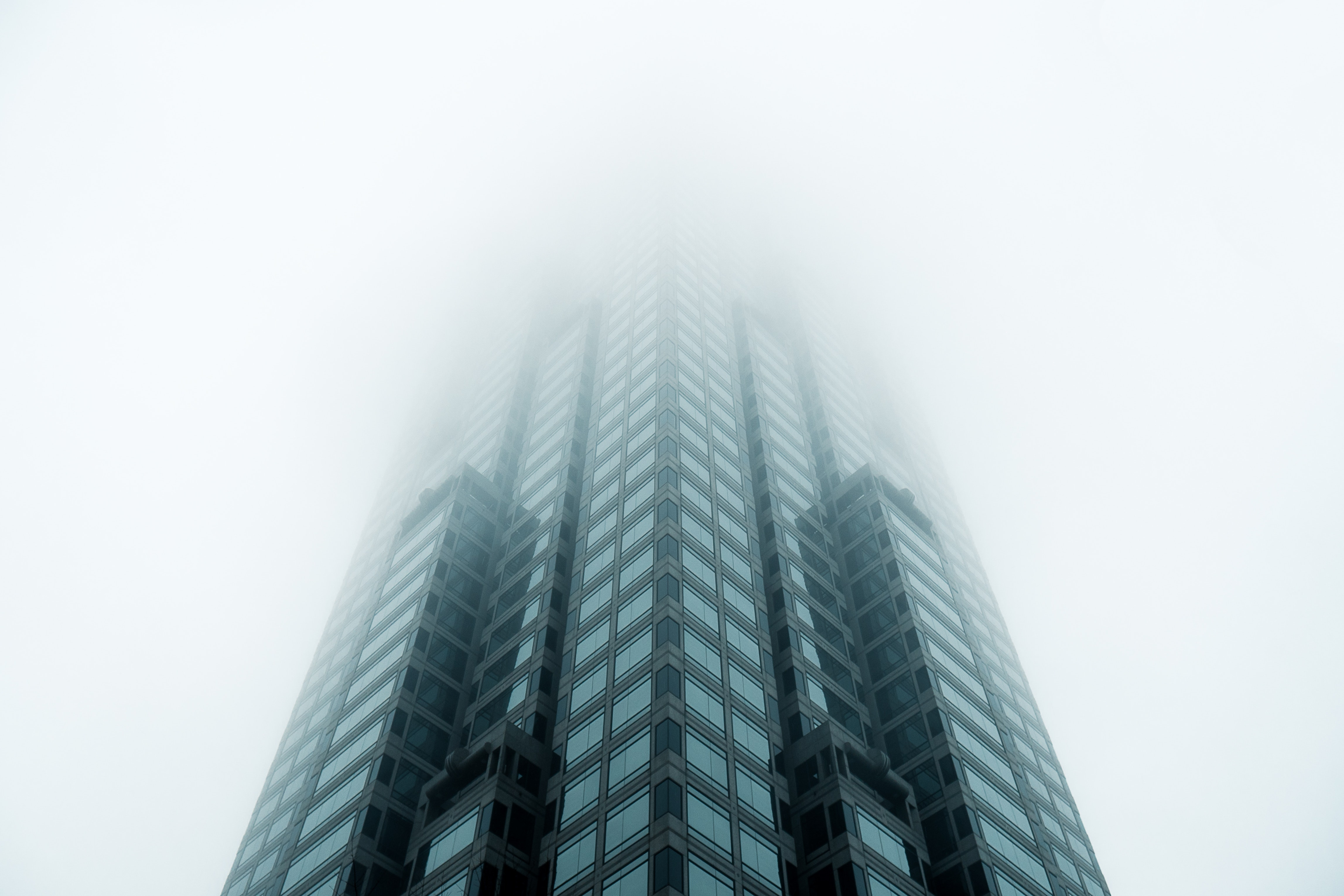 Low-angle photo of a high rise building standing in a fog