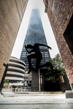Low-angle photography of a person jumping in front of a skyscraper