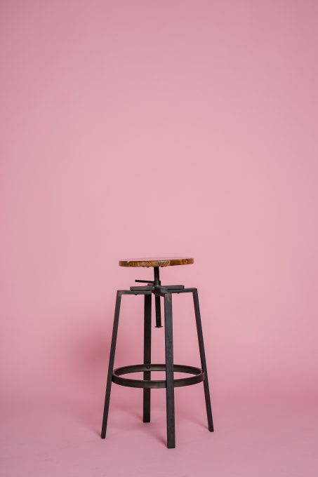 Metal stool in front of a pink background