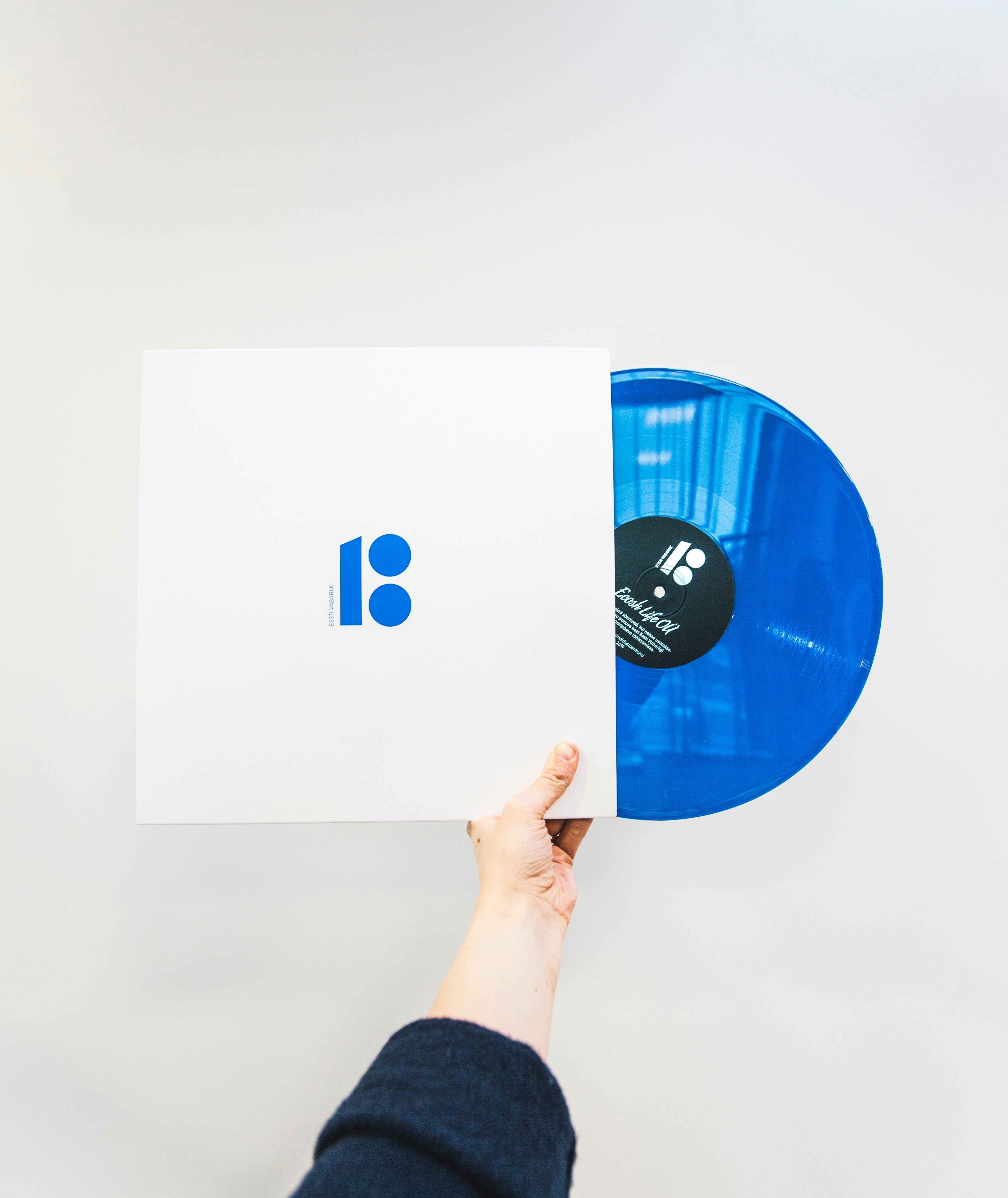Minimalist photo of a person holding a blue vinyl record