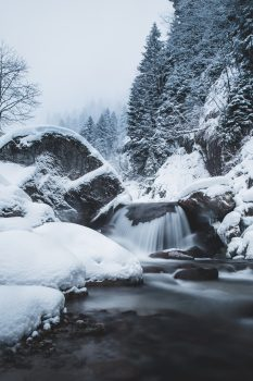 Photo of a waterfall in a snowy forest