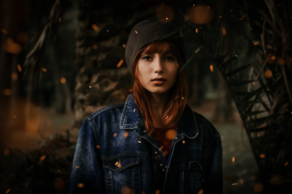 Photo of a young woman wearing a black hat and denim jacket