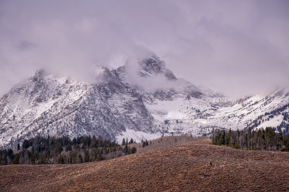 Photo of a snowy mountain under gray clouds