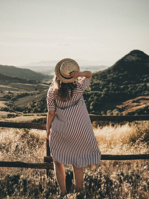 Selective focus photography of a woman holding a brown straw hat