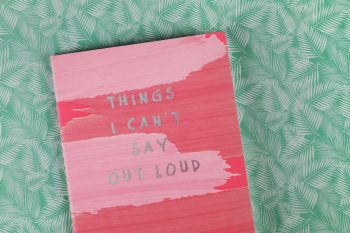 """""""Things I can't say out loud"""" book lying on a green textile"""