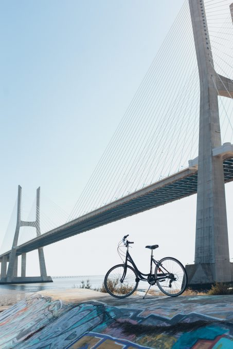 A bicycle parked under a gray concrete bridge