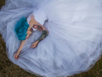 A blue-haired woman in a white lace wedding dress lying on green grass