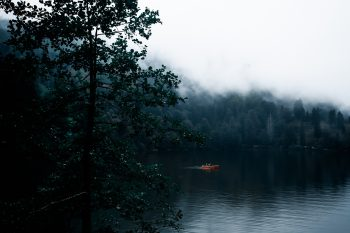 A boat floating on a lake in the fog