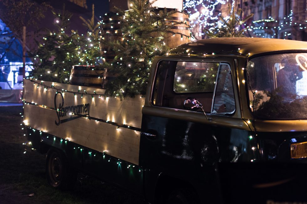 A classic brown single-cab truck with Christmas trees and string lights