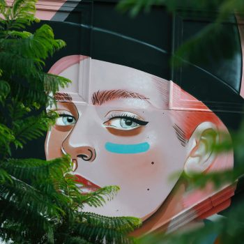 A colorful mural of a woman wearing black hat