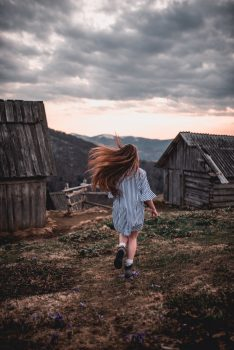 A girl running on a brown and green field on a cloudy day