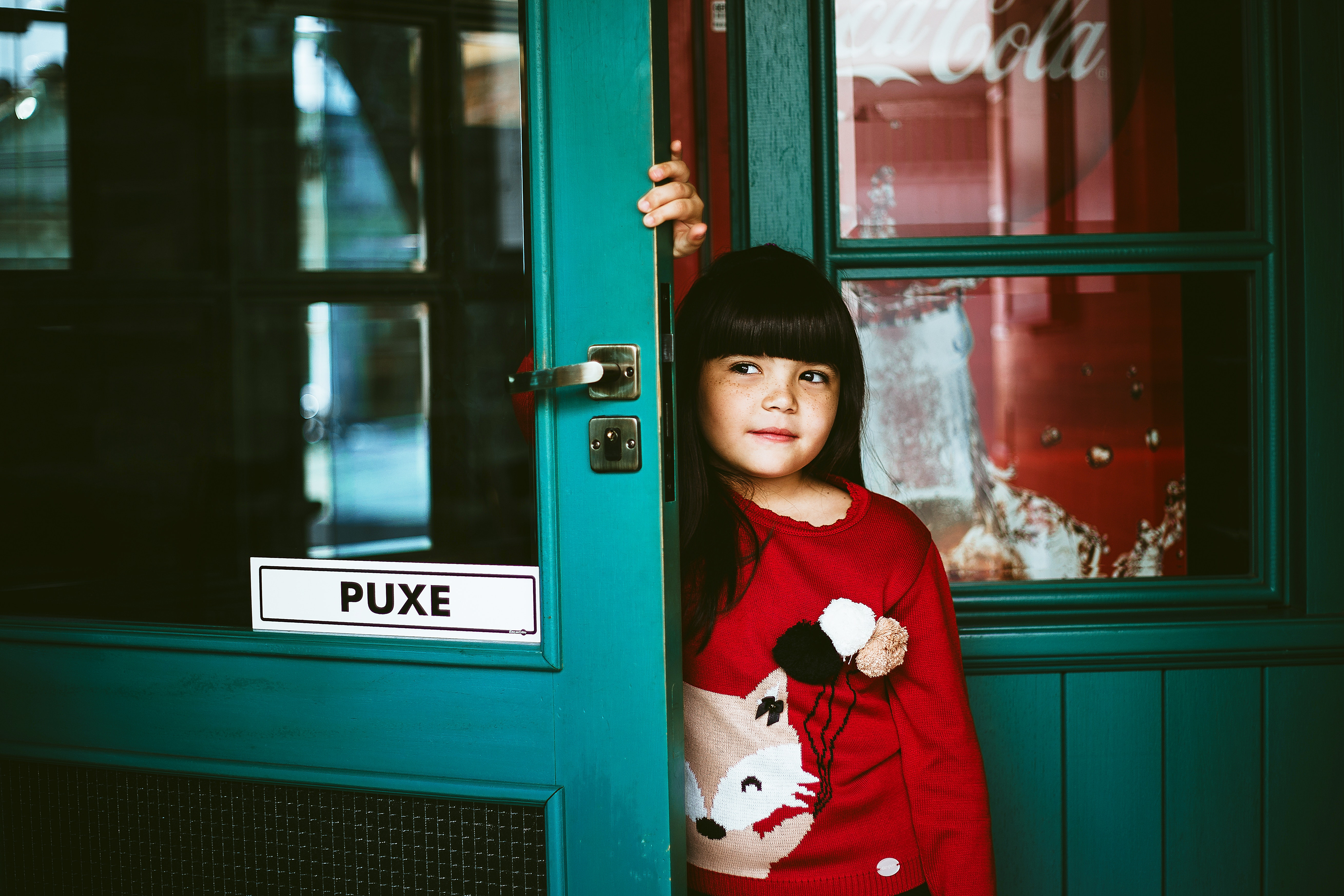 A girl wearing a red long-sleeved shirt leaning on a door