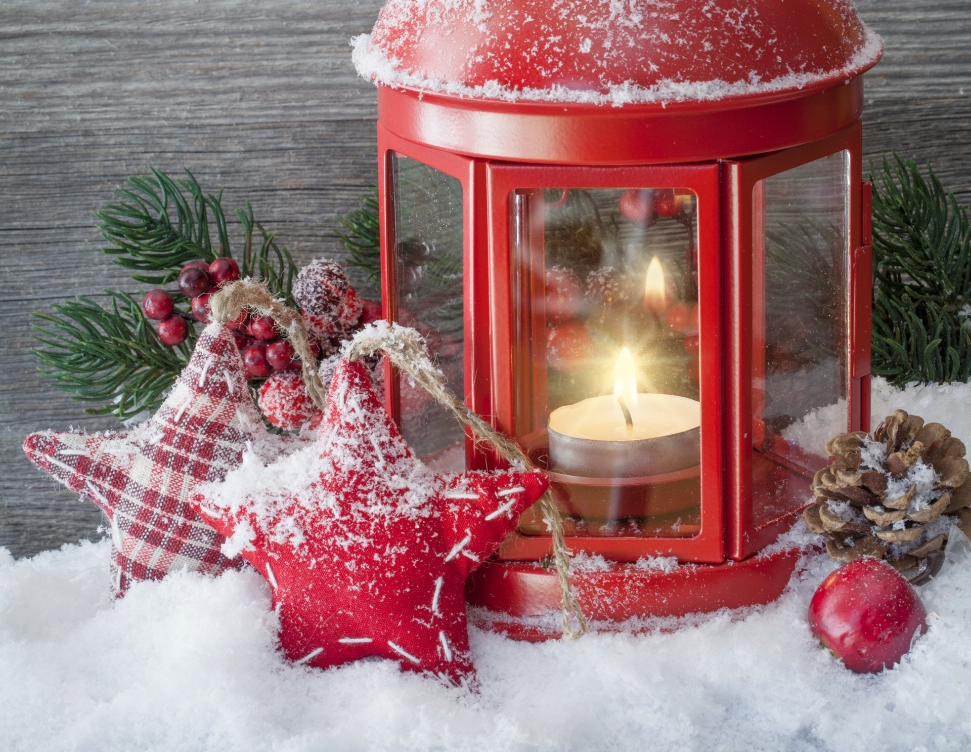 A lighted white tealight candle inside a red metal lantern