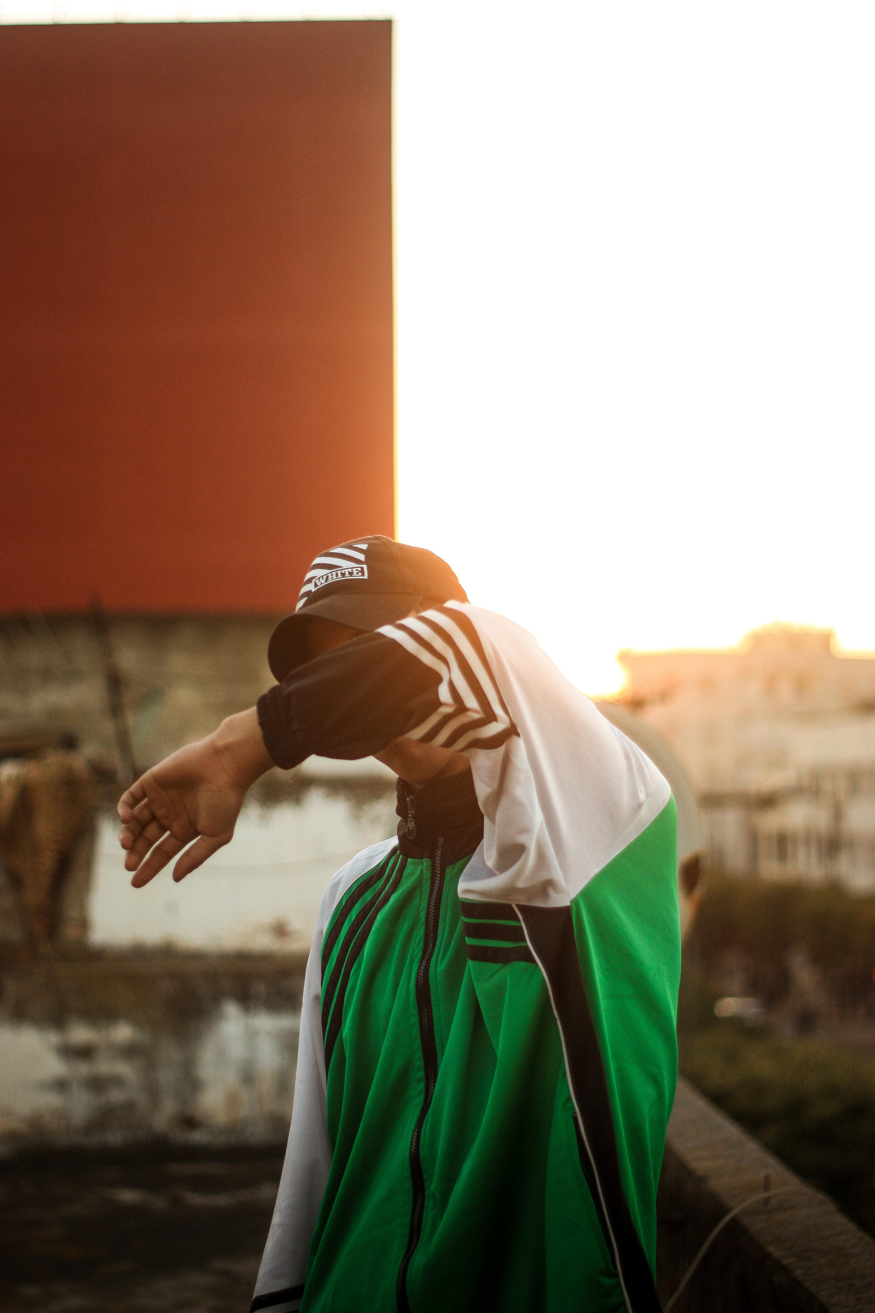 A man in sportswear covering his face