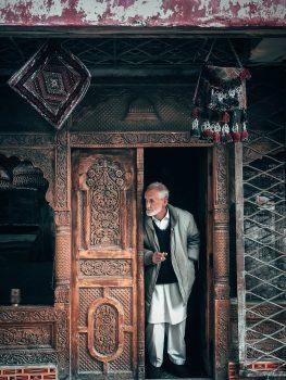 A man peeking behind doors