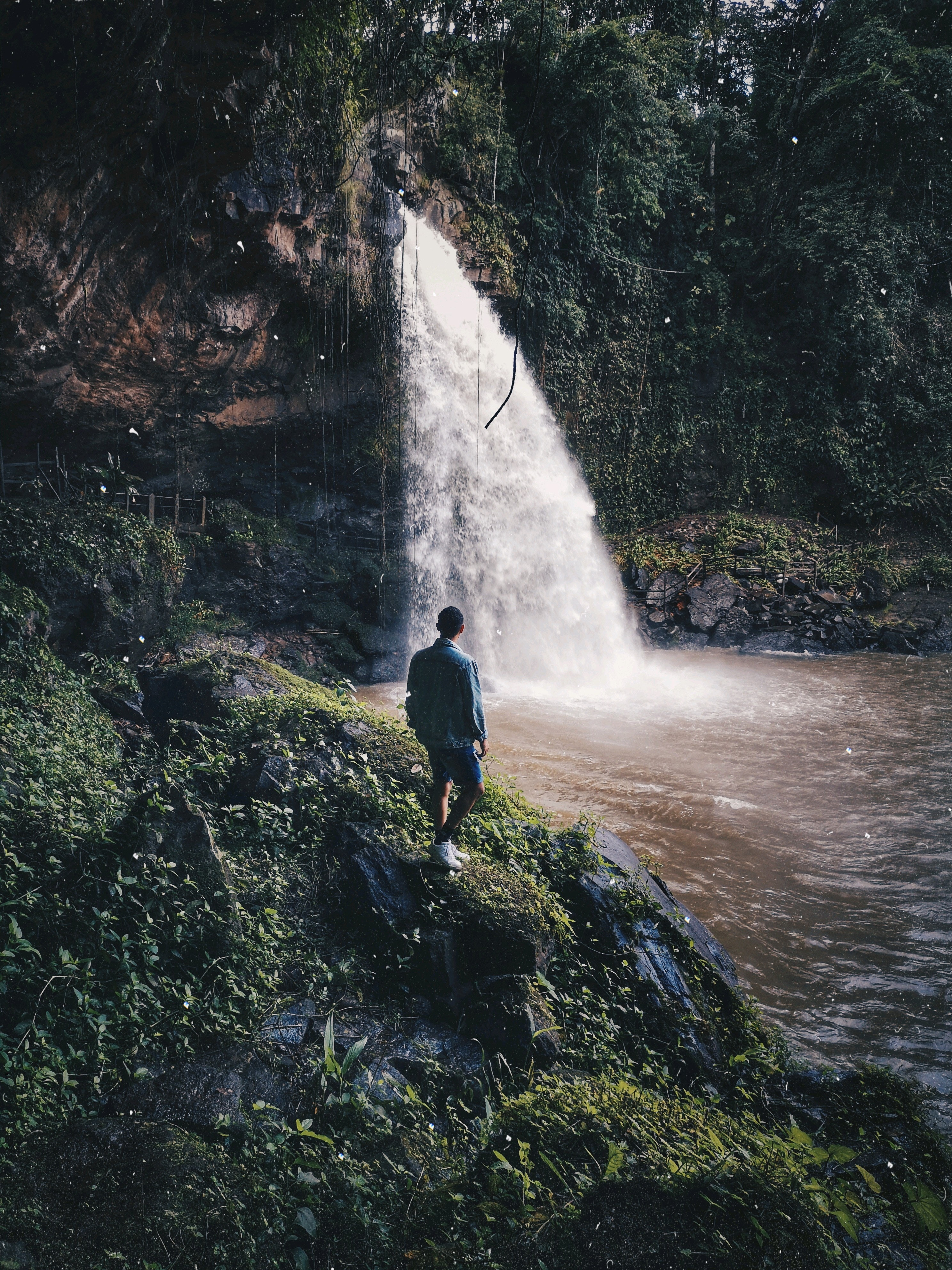 A man standing beside waterfalls