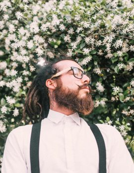 A man with dreadlocks and a beard wearing a white shirt and eyeglasses