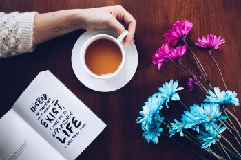 A person holding a cup of coffee beside a book and flowers