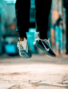 A person in Nike sneakers hovering above the ground