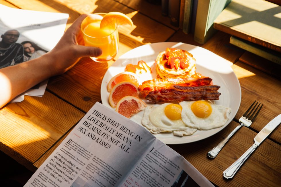 A person reading a newspaper during eating breakfast
