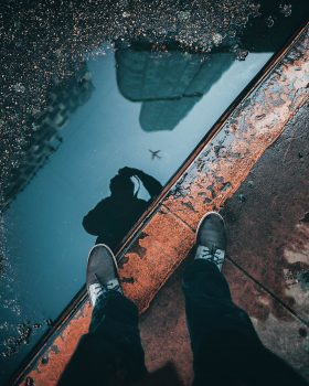 A person taking a photo of a puddle reflection of an airplane