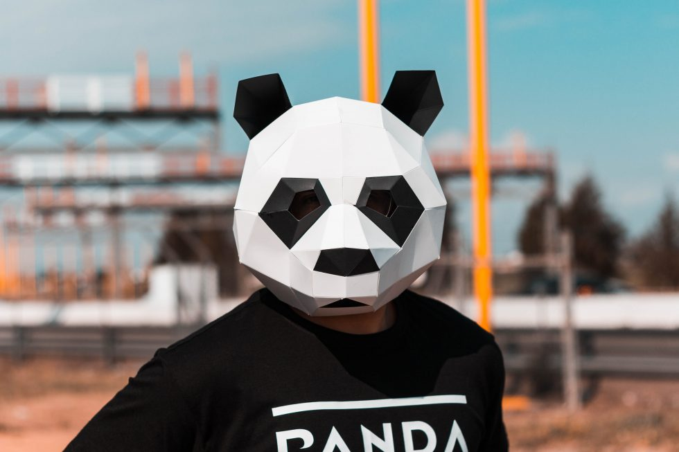 A person wearing a white and black panda full-face mask