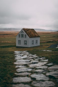 A turf house at a green field on a cloudy day