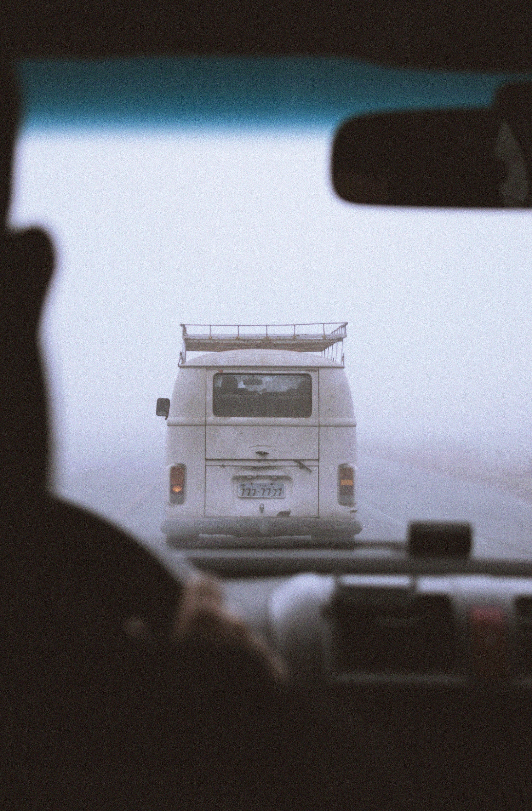 A white vehicle driving in fog