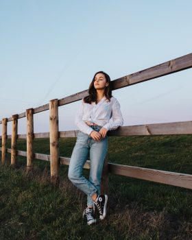 A woman leaning on a wooden fence while standing on a grass field