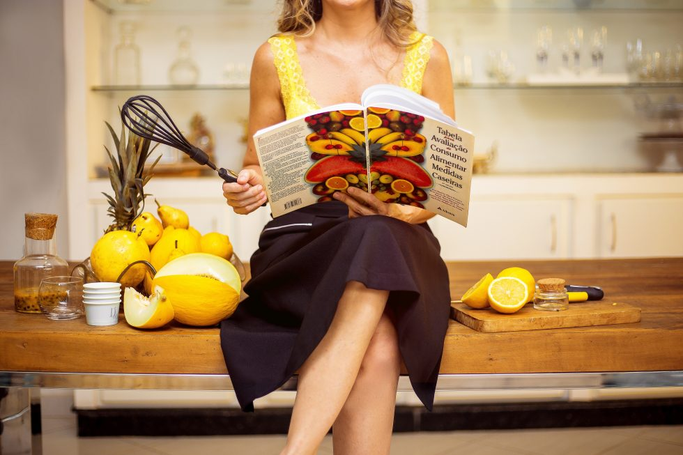A woman sitting on a table holding a black whisk and cookbook