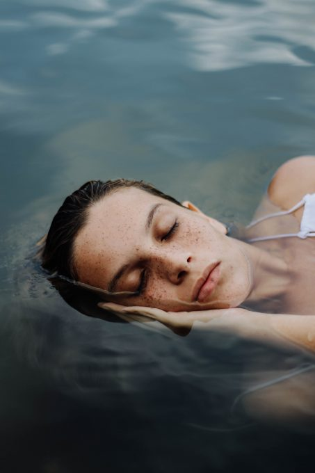 A woman sleeping on the body of water