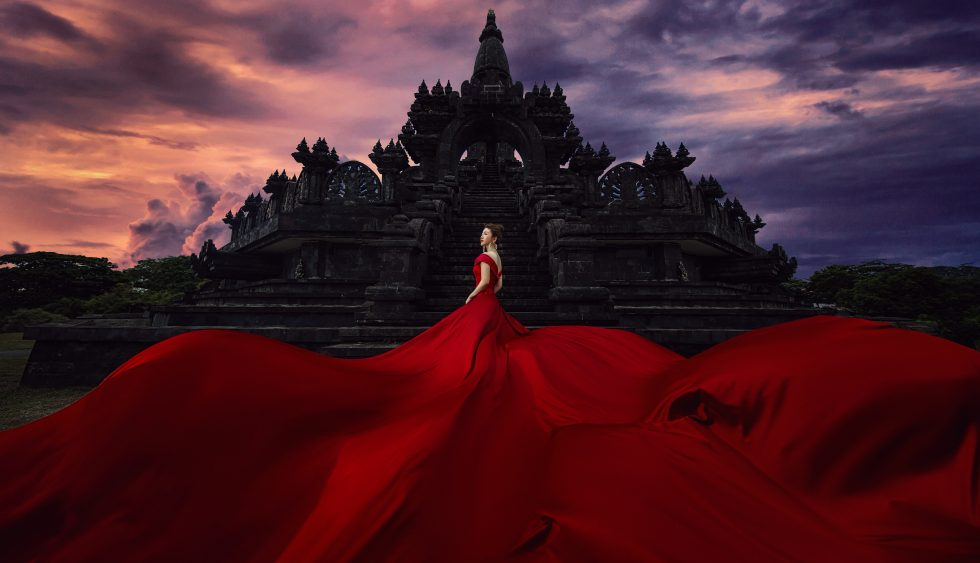 A woman wearing a red long dress outside a building