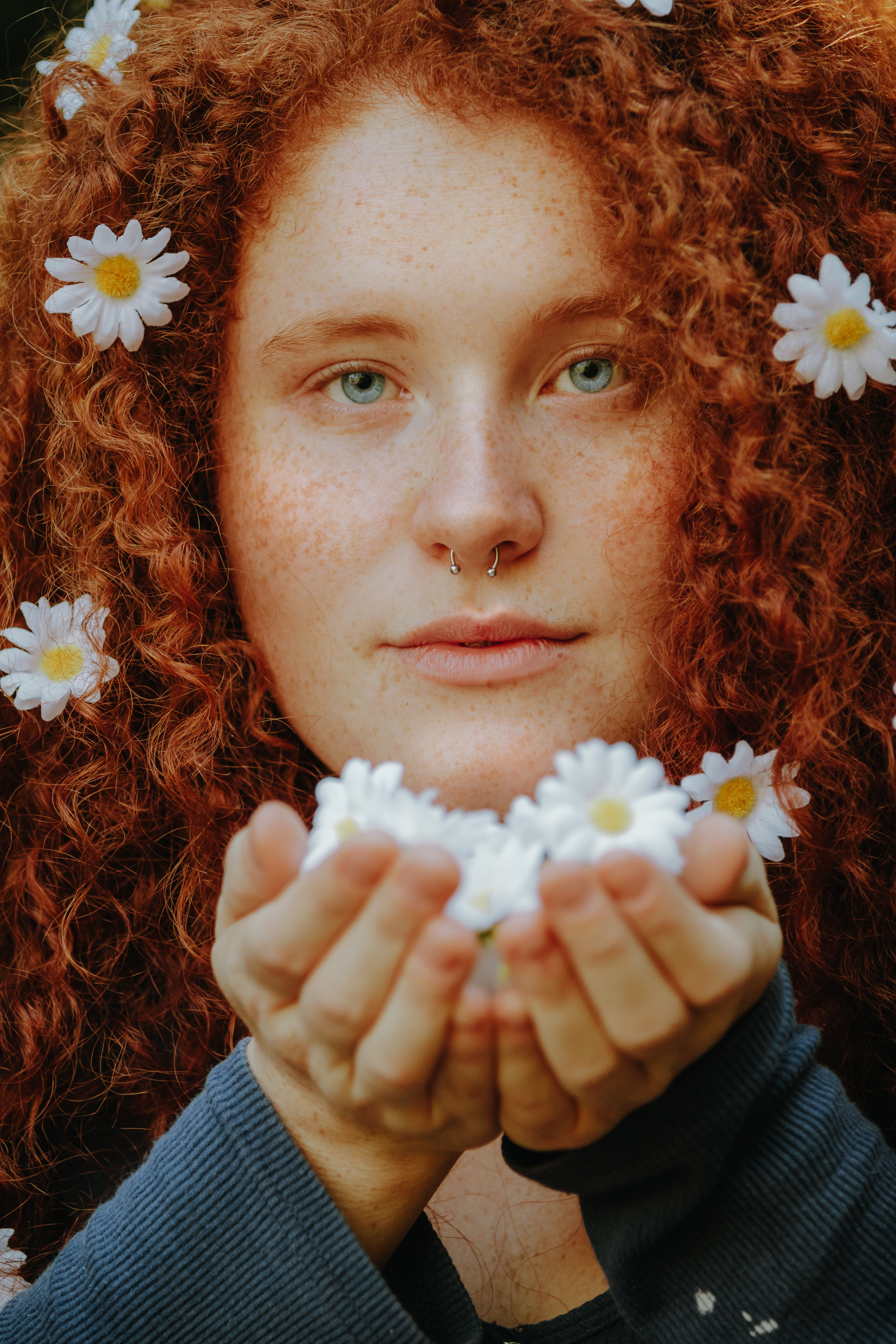 A woman with pierced nose holding daisies