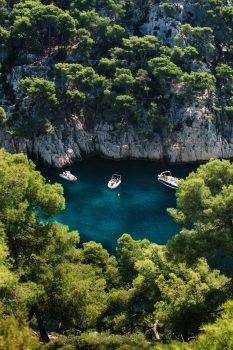 Aerial photo of speed boats at the middle of the sea surrounded by trees