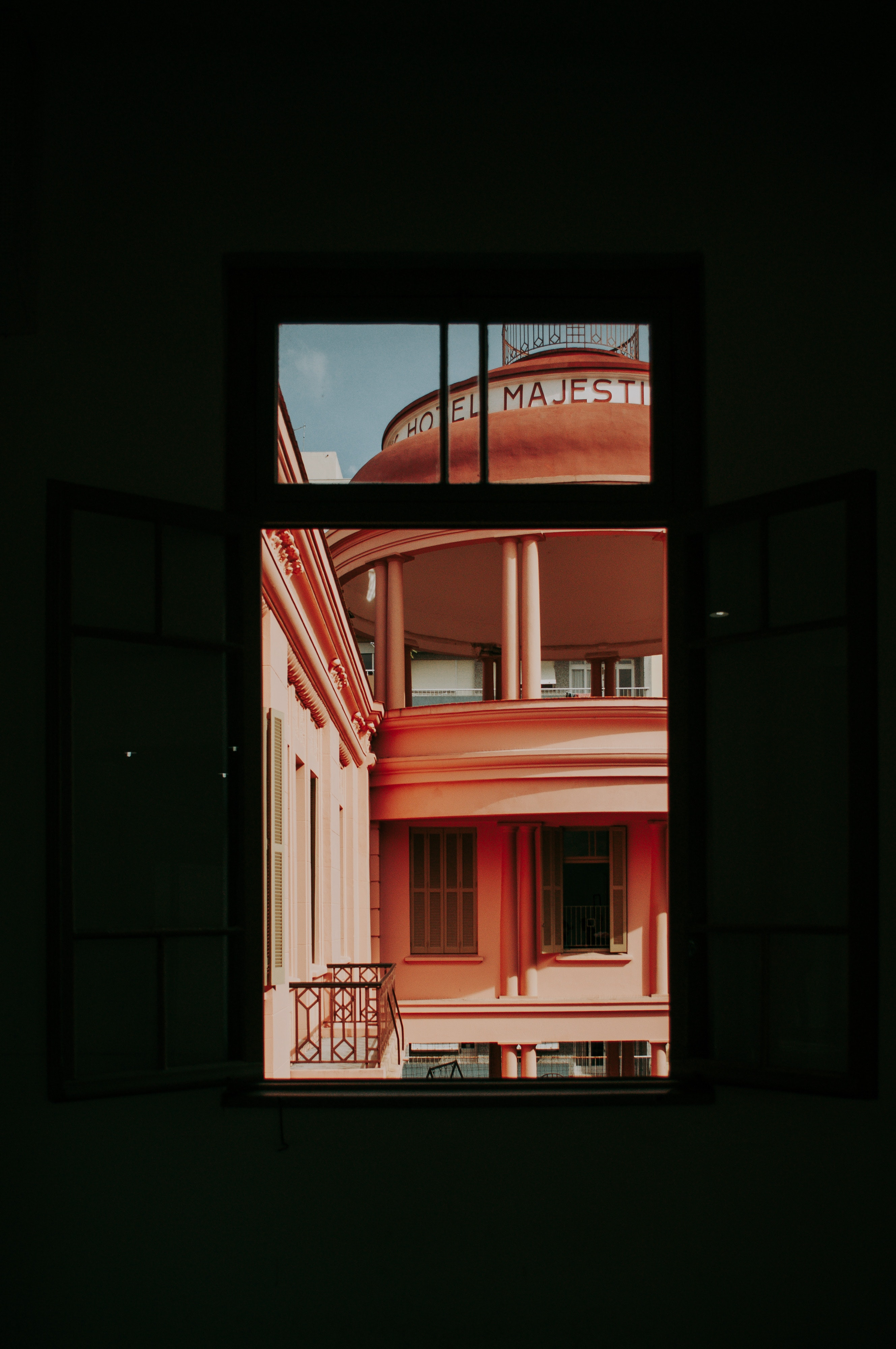 An orange painted building through a window