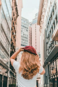 Back view of a girl in a red hat walking among tall buildings