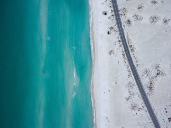 Bird's eye view of a road along a beach during daytime