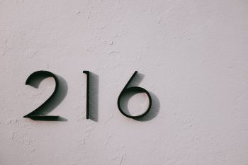 Black 216 number on a beige wall