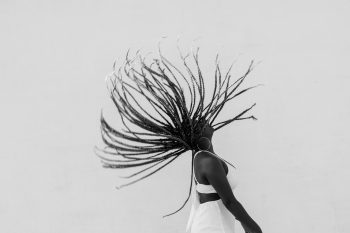 Black and white photo of a woman in a white dress throwing up her hair