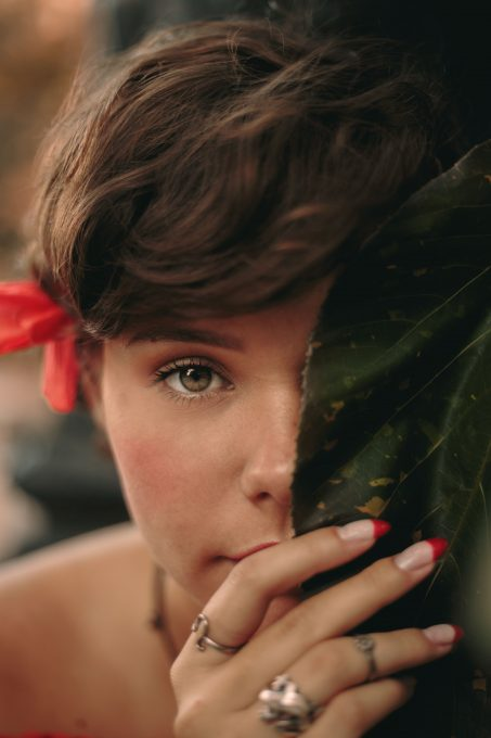 Close-up photo of a woman holding a leaf