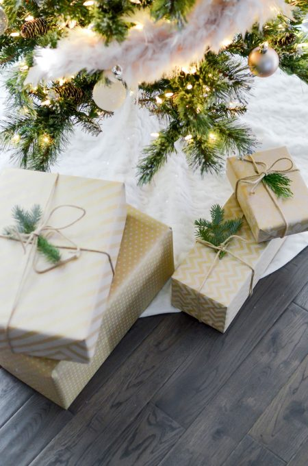 Four gift boxes near lighted string lights
