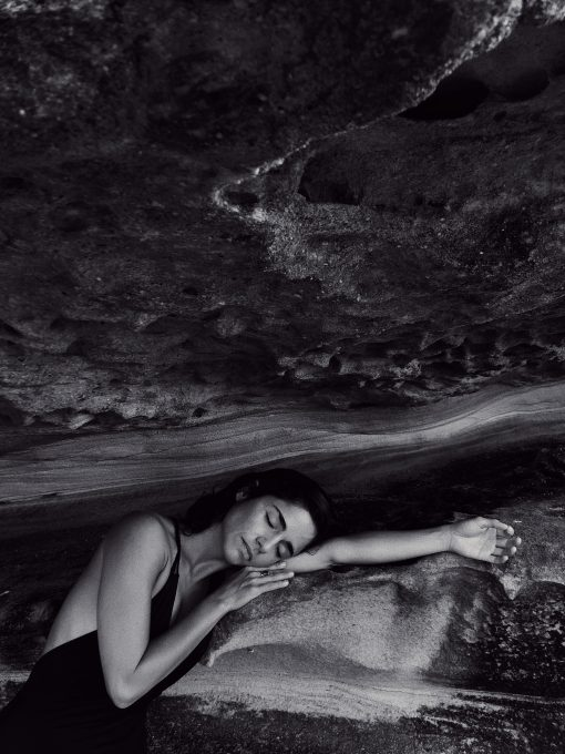 Grayscale photography of a woman leaning on a rock