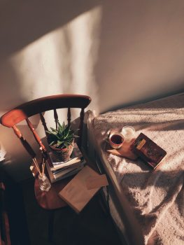 High-angle photo of a brown wooden chair beside a bed