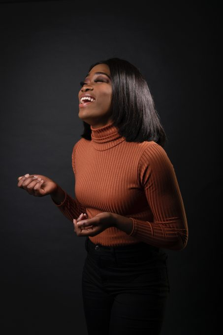 Laughing woman in a brown sweater against a black wall