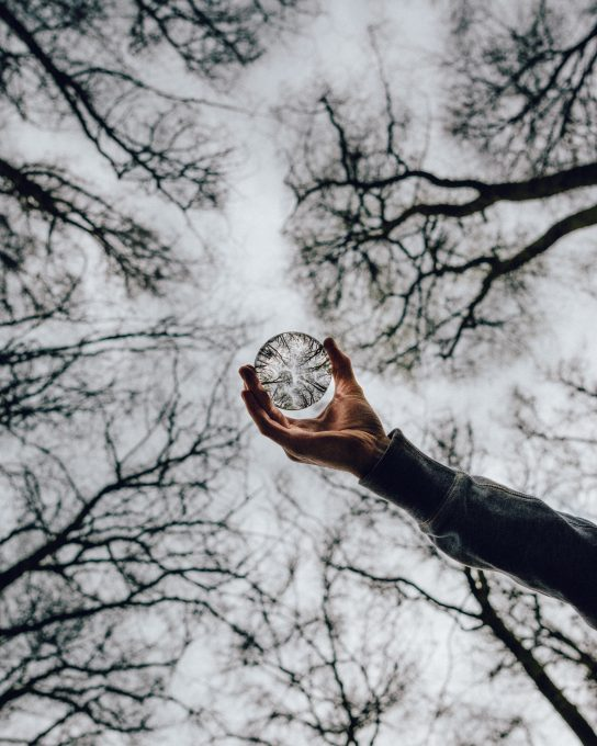 Low angle photo of a person holding a crystal ball