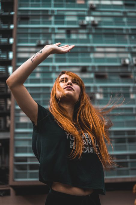 Low-angle photo of a woman raising her right hand