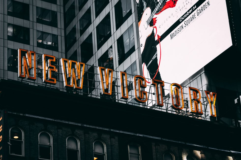 Low-angle photography of New Victory neon sign
