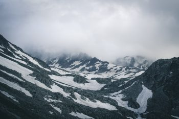 Mountains covered by snow during fog