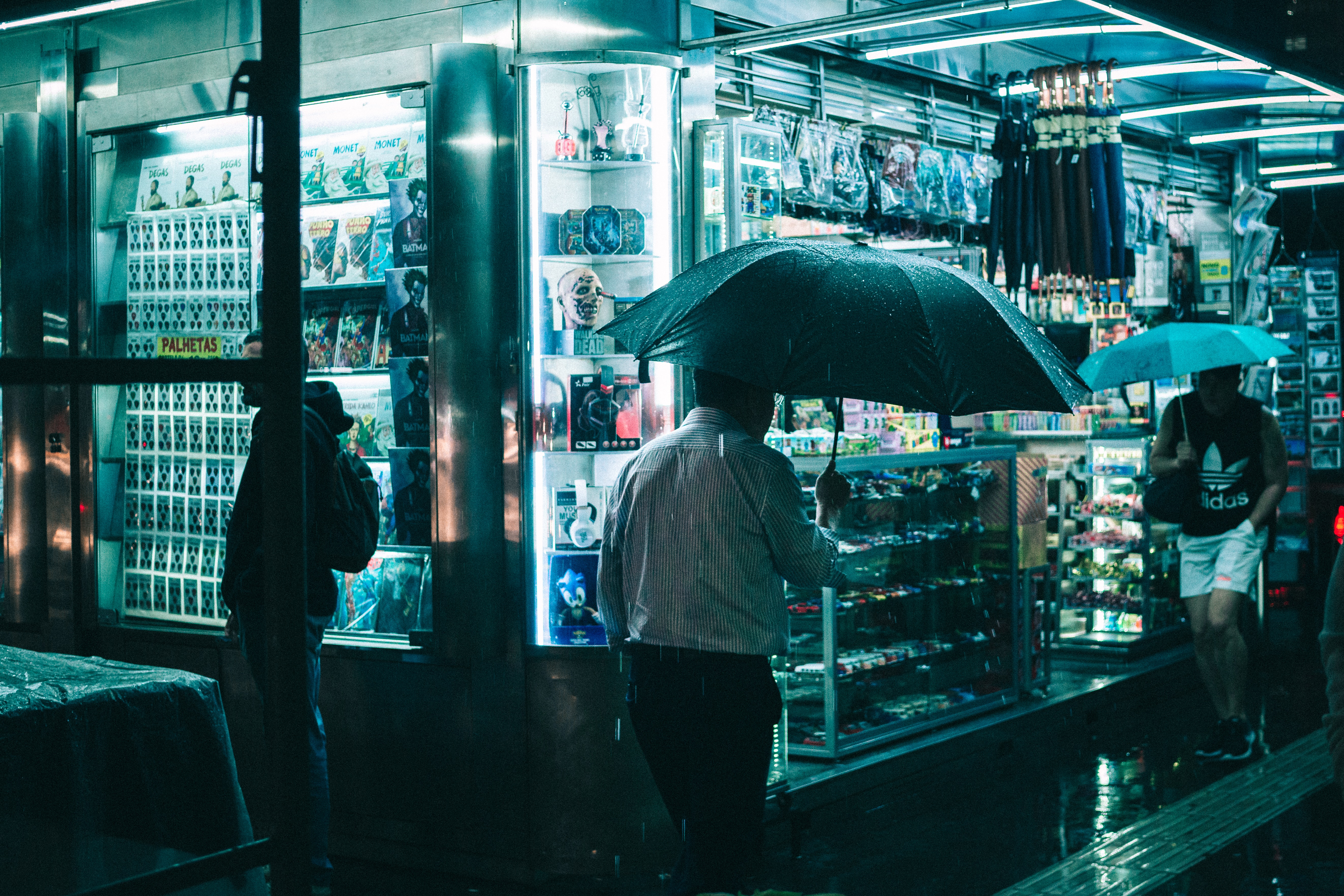 People walking along a sidewalk of a store in the evening in the rain